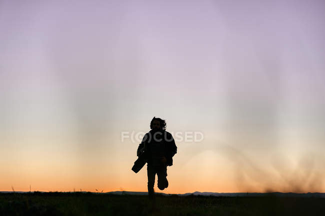 From below of dark silhouette of male musician with long hair running towards camera with guitar in hands at sunset — Stock Photo
