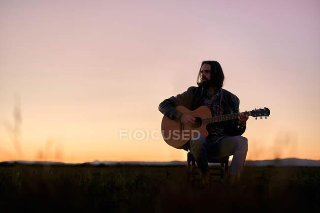 Bärtiger Gitarrist mit langen Haaren, der bei Sonnenuntergang auf einer Wiese sitzt, ein Musikinstrument in der Hand hält und Melodie spielt, während er nachdenklich wegschaut — Stockfoto