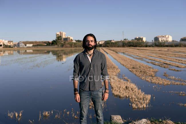 Hombre de pie frente al lago en la orilla entre la hierba amarilla corta junto al lago con los ojos cerrados - foto de stock