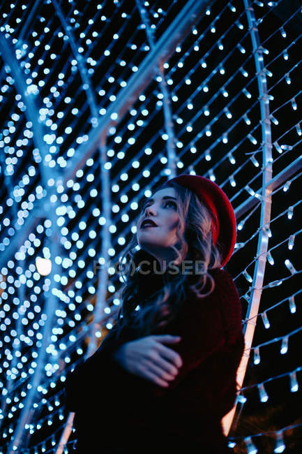 Elegante donna in abbigliamento alla moda e cappello vicino al muro con luci nel periodo natalizio — Foto stock