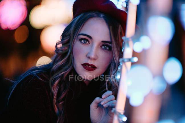 Елегантна жінка в модний одяг і капелюх біля стіни з вогнями в різдвяний час — стокове фото