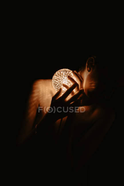 High angle of naked woman covering chest with hand and holding luminous ball in dark — Stock Photo
