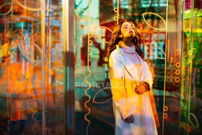 Hermosa dama con lápiz labial rojo en abrigo de moda y suéter de pie entre coloridos carteles de neón en la calle de la ciudad - foto de stock