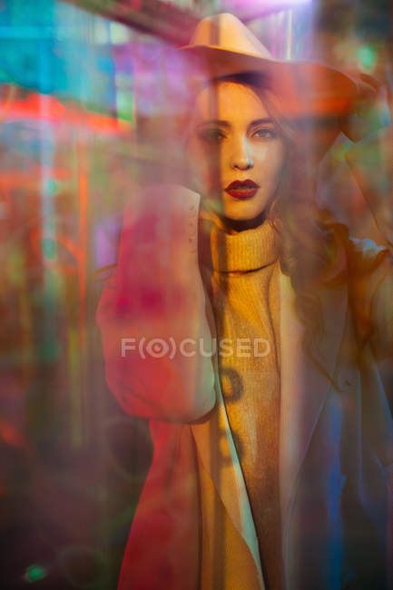 Sensual young woman with red lipstick looking in camera in light of neon signs at city street — Stock Photo