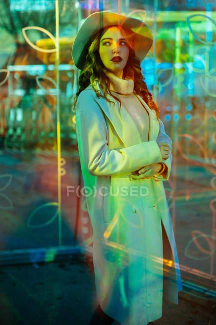 Stilvolle junge Frau im weißen Mantel blickt im Licht der Leuchtreklamen an der Stadtstraße weg — Stockfoto