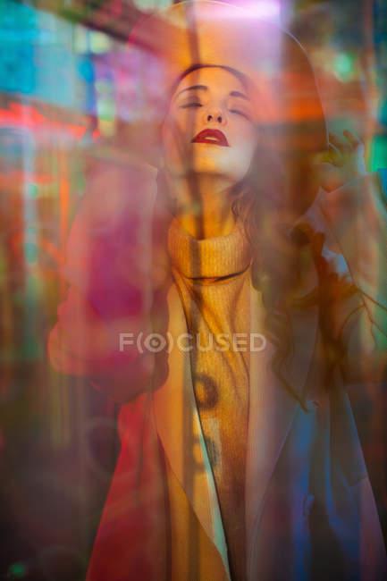 Hübsche junge Frau mit geschlossenen Augen im Licht der Leuchtreklamen an der Stadtstraße — Stockfoto