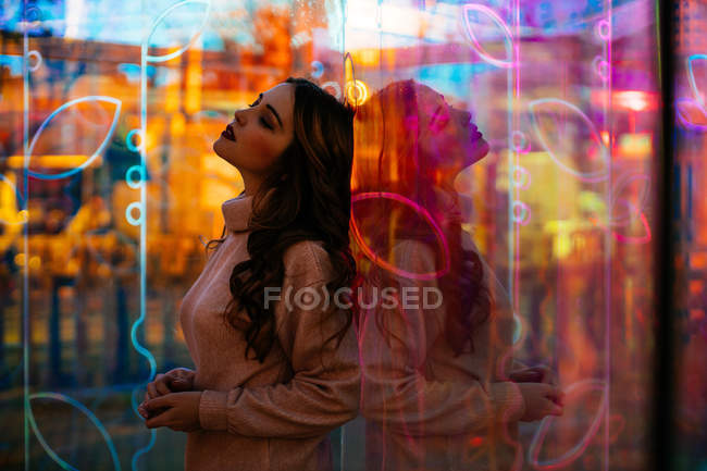 Young woman relaxing in light of neon signs with reflection on city street — Stock Photo