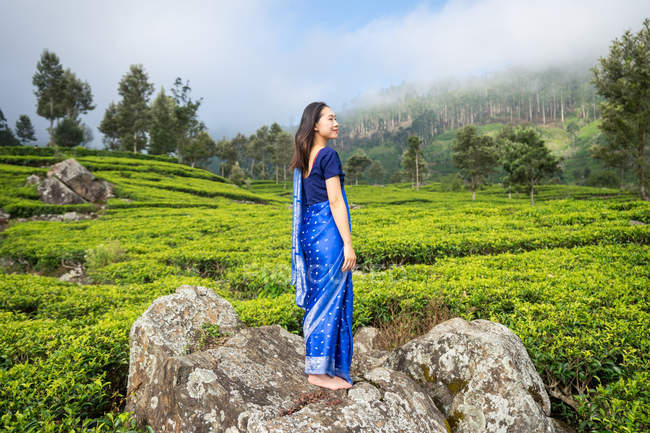Side view of satisfied young Asian woman in blue sari standing on rock in middle of tea fields in Haputale in Sri Lanka — Stock Photo