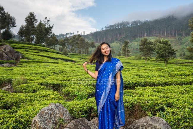 Vista lateral da mulher asiática em sari azul em pé na rocha olhando para a câmera no meio de campos de chá em Haputale, no Sri Lanka — Fotografia de Stock