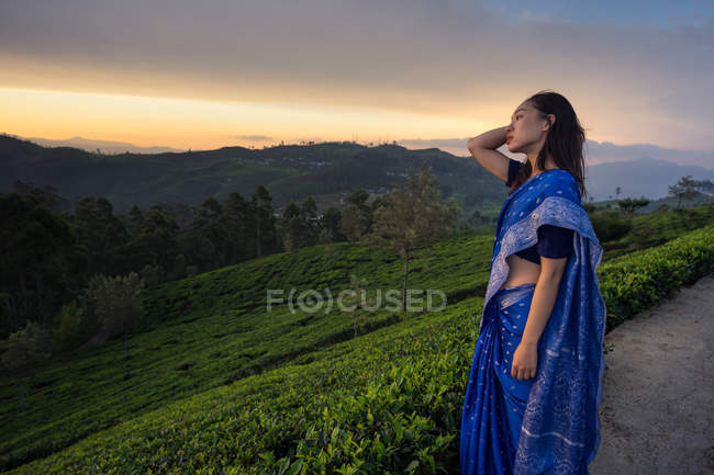 Side view of woman in blue sari watching at picturesque sundown while standing on tea fields in Haputale in Sri Lanka — Stock Photo