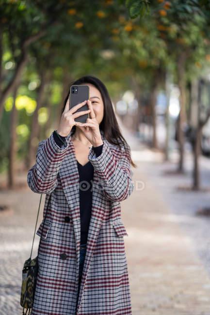 Mujer asiática en chaqueta a cuadros con bolso que se centra en la pantalla y toma fotos con teléfono inteligente - foto de stock