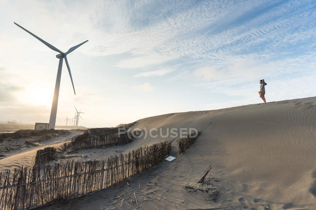 From below of traveler on sandy hill delighting in vacation with blue sky and windmills on background at Taiwan — Stock Photo