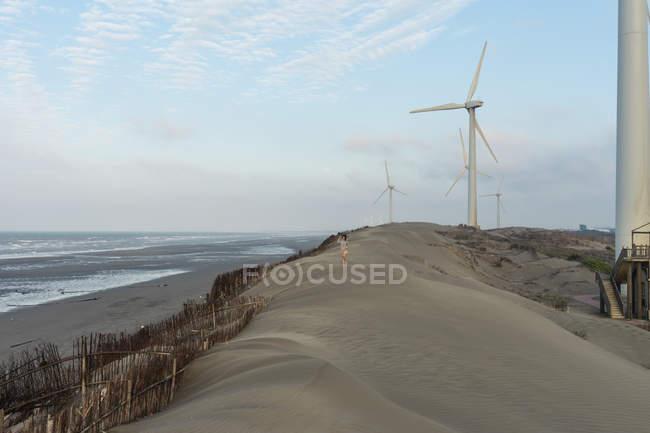 Lonely tourist on sandy hill near windmills — Stock Photo
