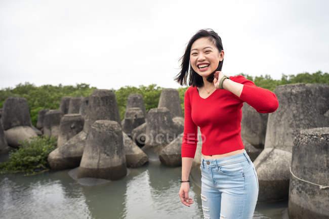 Радостная азиатская женщина в повседневной одежде, смеющаяся во время прогулки по раскачивающемуся пруду с небом на заднем плане — стоковое фото