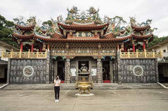 Жіночий мандрівник у повсякденному одязі, який фотографує перед камерою з прекрасним даоським храмом Дай Куан Тан на Тайвані. — стокове фото