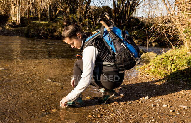 Woman hiker in sports boots splashing in creek water — Stock Photo