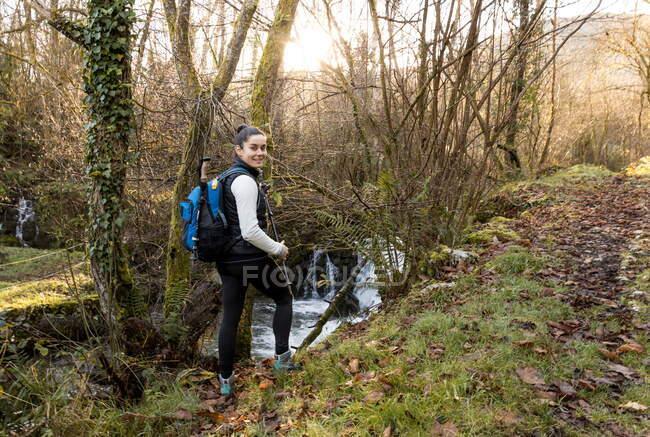 Escursionista femminile con zaino esplorare foresta — Foto stock