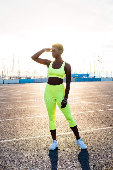 Serious focused African American woman in vibrant yellow sportswear looking away and contemplating in sunbeams alone on street against urban environment — Stock Photo