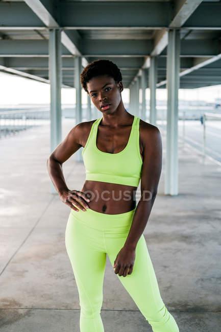 Взрослая афроамериканская спортсменка в ярко-зеленой спортивной одежде, стоящая в одиночестве вдоль набережной среди металлических колонн под крышей — стоковое фото