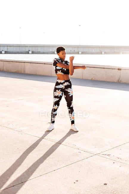 Femme adulte afro-américaine en vêtements de sport fleuris étirant les muscles de la main tout en restant seule et en se réchauffant avant de s'entraîner dans un environnement urbain par temps ensoleillé — Photo de stock