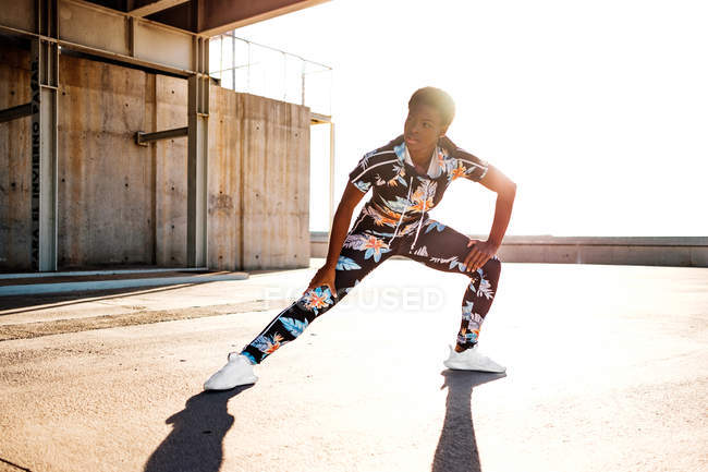 Femme adulte afro-américaine en tenue de sport fleurie étirant les muscles des jambes tout en restant seule et en se réchauffant avant de s'entraîner dans un environnement urbain par temps ensoleillé — Photo de stock