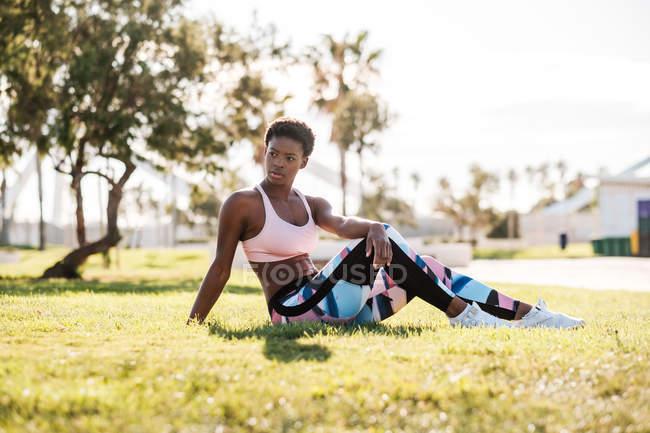 Athlète afro-américaine en vêtements de sport colorés et baskets blanches regardant loin avec curiosité tout en étant assis sur l'herbe verte sur la pelouse et se reposant après l'entraînement — Photo de stock