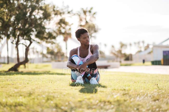 Afro-americano atleta feminina em activewear colorido e tênis brancos olhando para longe com curiosidade enquanto sentado na grama verde no gramado e descansando após o treinamento — Fotografia de Stock
