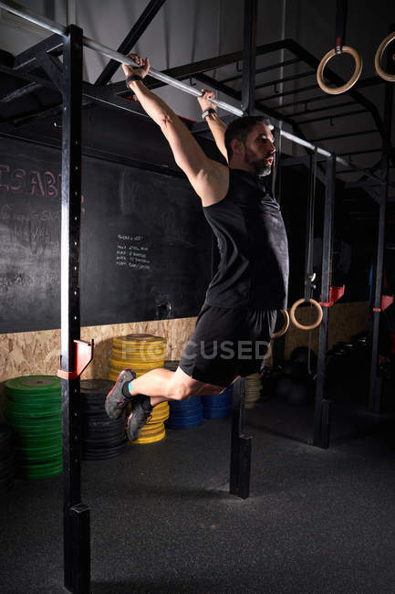 Strong man doing strength exercise on bar in gym with magnesium in hands. — Stock Photo