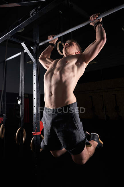 Young male athlete practicing on cross fit gym bar while multidisciplinary training. — Stock Photo