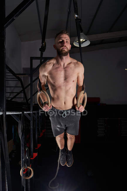 Strong man doing strength exercise on gymnastic rings in cross fit gym. — Stock Photo