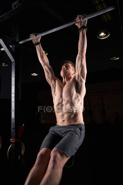 Young man doing pulling up exercise on bar in gym with magnesium in hands. — Stock Photo