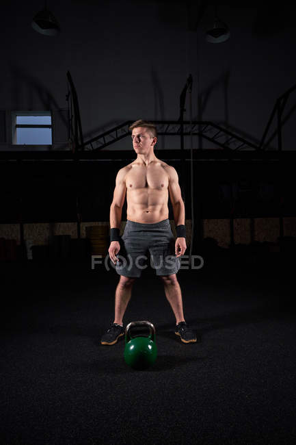 Shirtless young male muscular athlete preparing for weights training in gym. — Stock Photo