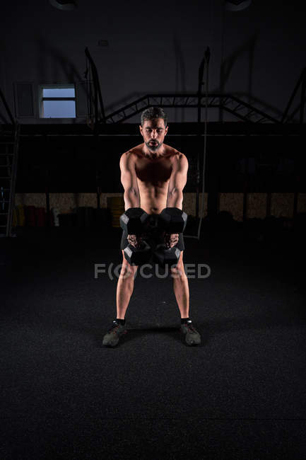 Strong mature man lifting dumbbells as doing strength exercise in gym with magnesium in hands. — Stock Photo