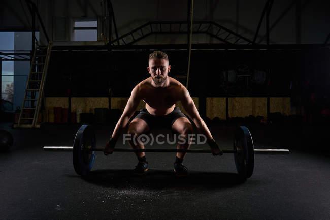 Un gran atleta masculino que practica el ejercicio con campana en el gimnasio de musculación como práctica de entrenamiento multidisciplinar.. - foto de stock