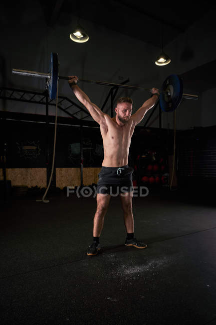 Strong male athlete exercising with barbell in cross fit gym as practicing multidisciplinary training. — Stock Photo