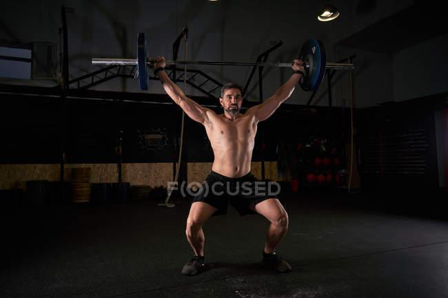 Спортсмен поднимает штангу в тренажерном зале для кросс-фитнеса в качестве упражнения на многоборье. — стоковое фото