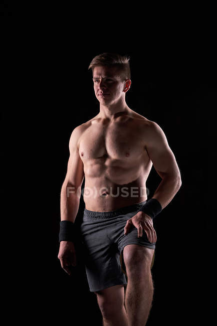 Strong muscular young man posing shirtless in gym. — Stock Photo