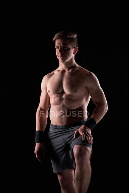 Forte muscolare giovane uomo posa shirtless in palestra. — Foto stock