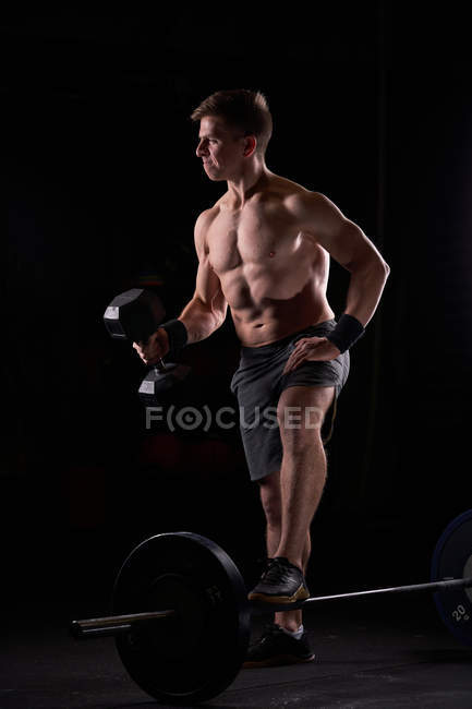 Strong muscular young man posing shirtless with barbell and dumbbell in gym. — Stock Photo