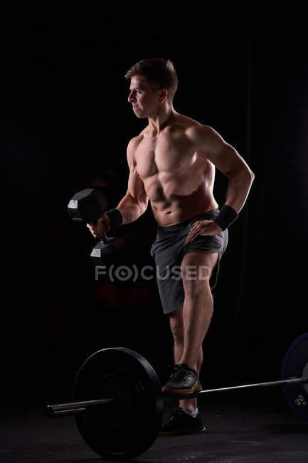 Строгий мускулистый молодой человек позирует в спортивном зале без штанги и гантелей. — стоковое фото
