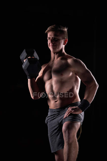 Strong muscular young man posing shirtless with dumbbell in gym. — Stock Photo