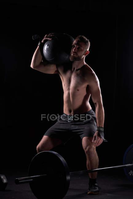 Forte muscolare giovane uomo posa shirtless con attrezzature pesanti in palestra. — Foto stock