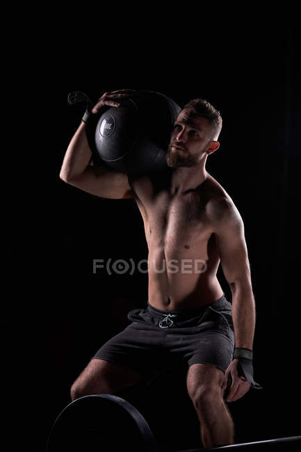 Strong muscular young man posing shirtless with heavy equipment in gym. — Stock Photo