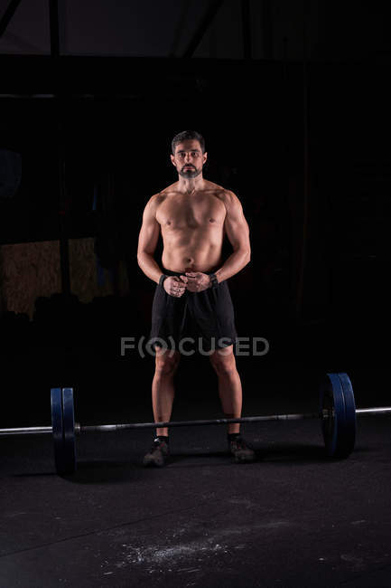 Strong muscular young man posing shirtless with barbell in gym. — Stock Photo
