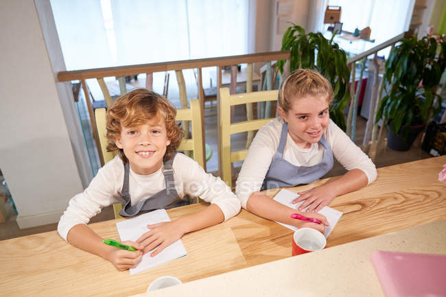 Children sitting in kitchen and writing with markers on paper. - foto de stock