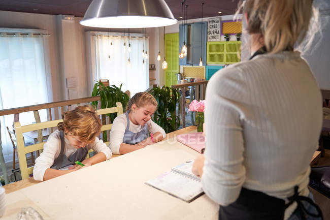 Children sitting in kitchen and writing with markers with woman reading recipe from notebook in hands. - foto de stock