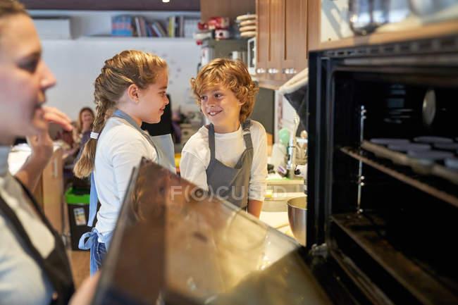 Zwei Kinder schauen sich an, während die Frau den Ofen zumacht — Stockfoto