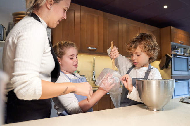 Boy and girl in aprons tucking cream from bowl into pastry bag as mother watching — Stock Photo
