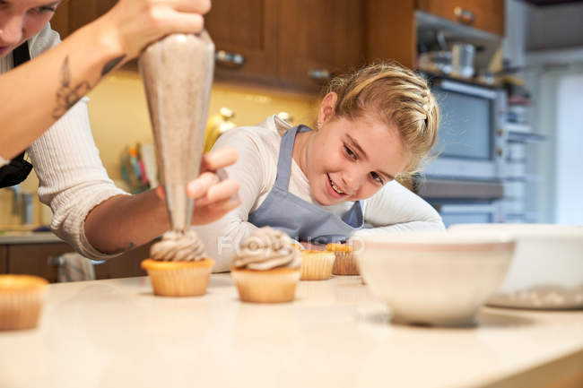 Woman decorating cupcakes with cream with pastry bag with girl smiling and watching — Stock Photo