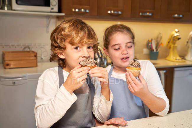 Двое счастливых малышей в апронах едят домашние кексы на кухне — стоковое фото
